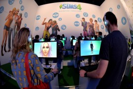 Visitors try out the game 'SIMS 4' at the Electronic Arts stand at the 2014 Gamescom gaming trade fair on August 14, 2014 in Cologne, Germany. Gamescom is the world's largest gaming convention and this year includes over 600 exhibitors.
