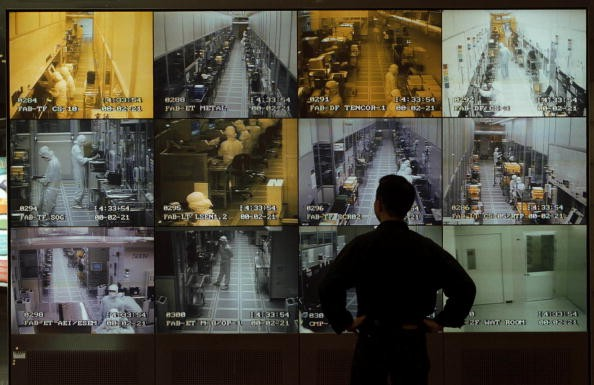 A visitor to United Manufacturing Corporation observes semiconductor manufacturing on wall of monitors in the company's reception area, Hsinchu, Taiwan, May 1, 2000.